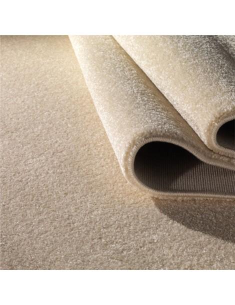 Dettaglio del tappeto minimalista a tinta piatta creama